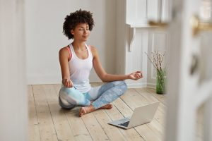 Relaxed dark skinned woman with sporty body, sits in zen pose, keeps legs crossed, watches yoga lessons on laptop computer using internet, meditates on floor in empty room.
